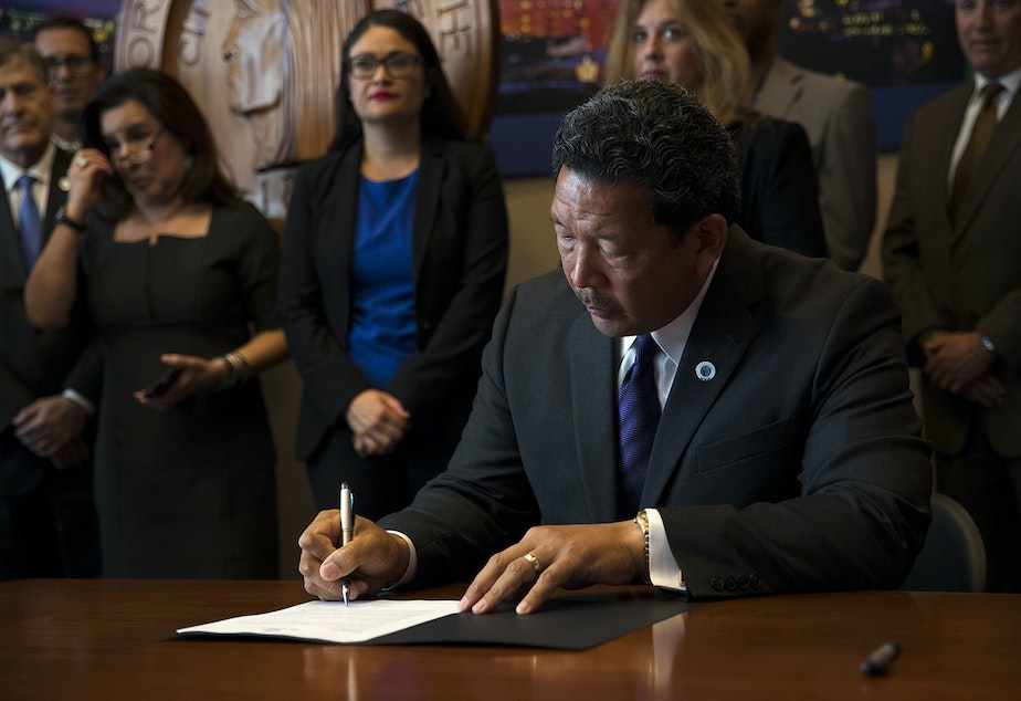 Seattle City Council President Bruce Harrell signs an executive order on Wednesday, September 13, 2017, after taking the oath of office and becoming the mayor of Seattle at City Hall.