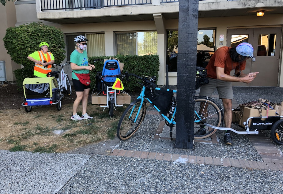 caption: From left, bike volunteers Janine Jordan, Ellen Nichter, and David Urbina prepare to deliver boxes of food and produce to families at this White Center apartment building.