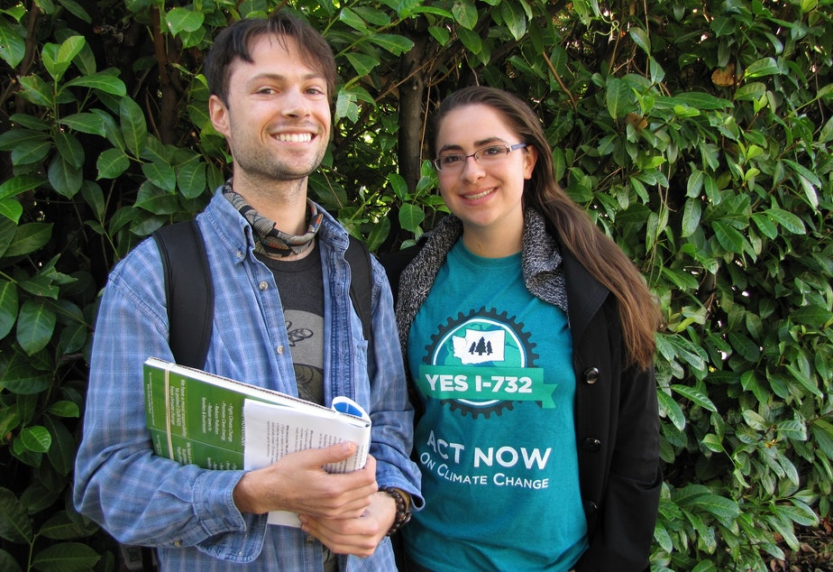 caption: Ben Silesky, 26, and Sydney Allen, 21, go door to door to raise awareness and support for ballot Initiative 732, which would put a tax on carbon emissions in Washington.