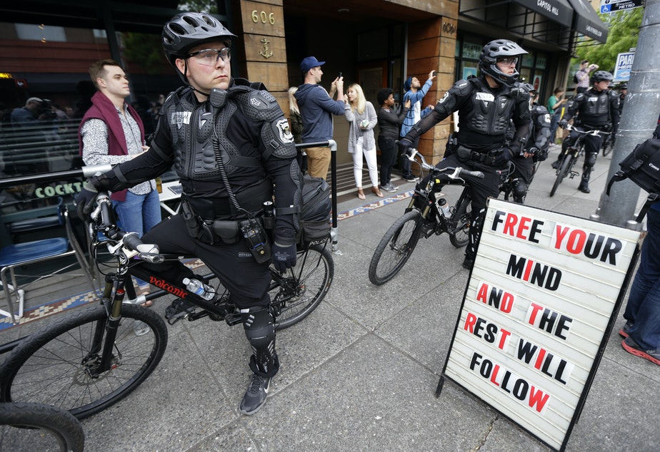 caption: Police officers pause next to a sign outside a restaurant as they observe a May Day anti-capitalism march, Friday, May 1, 2015 in Seattle.