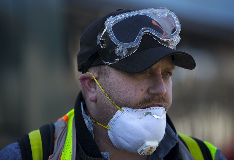 caption: Larry Bowles, an equipment service worker with King County Metro, wears a mask and goggles ahead of spraying a Virex II cleaning solution on the interior of a King County metro bus on Wednesday, March 4, 2020, at the Atlantic Base on 6th Avenue South in Seattle.