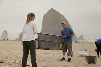 <p>Valerie Schockelt (left) and Kerry Lyons use a microplastics filtration device to filter sand on Cannon Beach with iconic Haystack Rock in the background.</p>