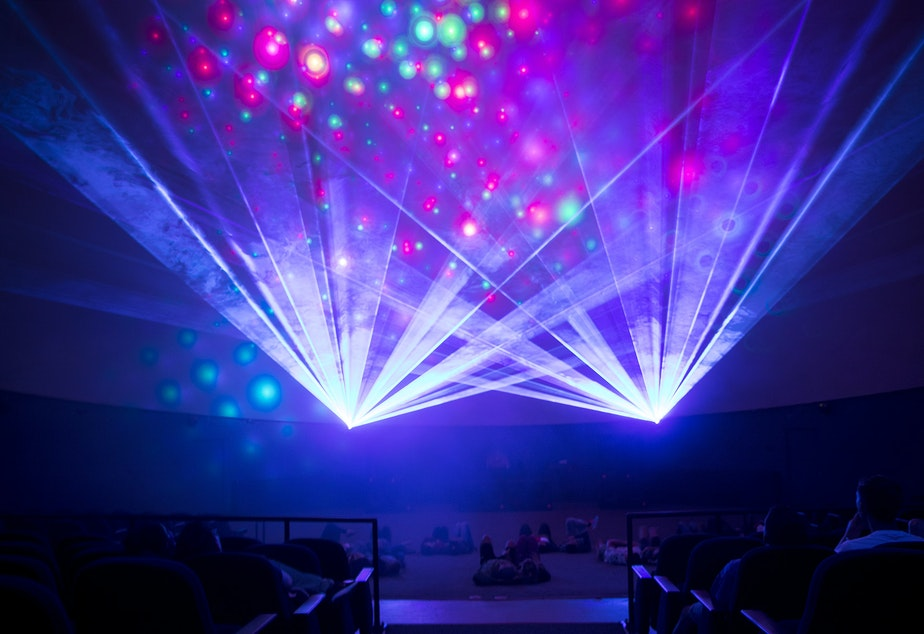 People lay on the floor of the Laser Dome on Thursday, May 17, 2018, during Laser Beyonce, by laser artist Gabriel Espinoza, at the Pacific Science Center in Seattle.