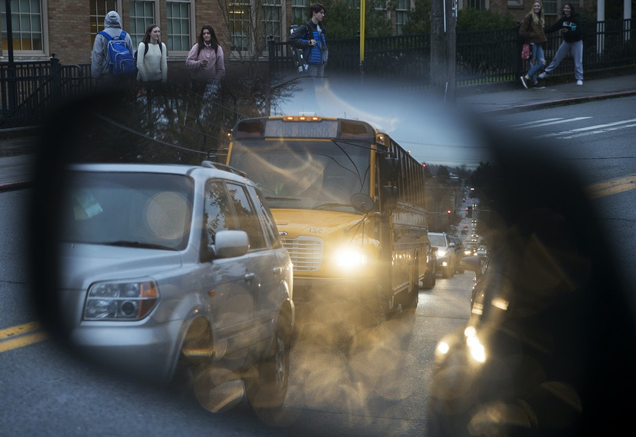 caption: A school bus is shown in vehicle's mirror as students pour out of Roosevelt High School on Tuesday, January 8, 2019, in Seattle.