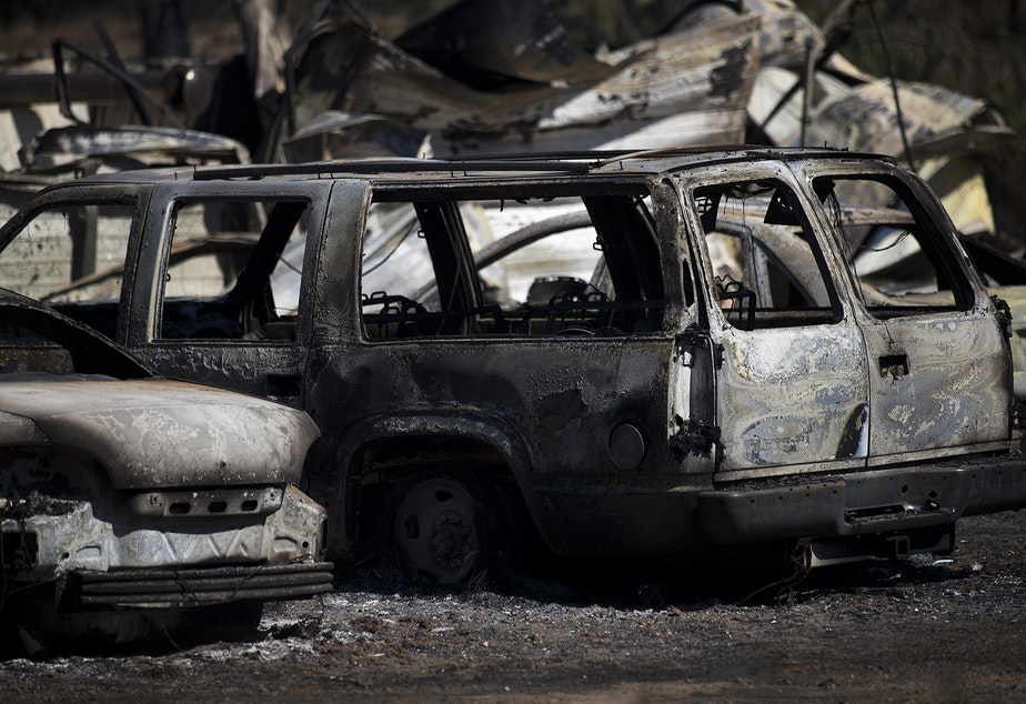 caption: Burned vehicles are shown on Wednesday, September 9, 2020, after a fire that started Monday evening burned 275 acres, including multiple homes and forced evacuations in the rural Pierce County town of Graham.