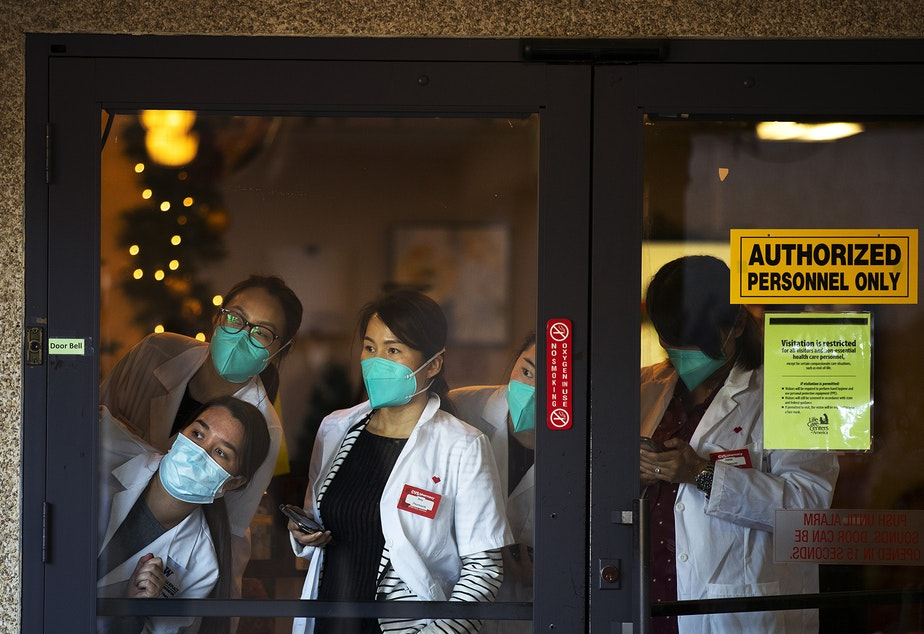 caption: Pharmacists with CVS look out of the front entrance of the Life Care Center of Kirkland ahead of the administration of the first Pfizer-BioNTech Covid-19 vaccinations for staff members on Monday, December 28, 2020, in Kirkland.