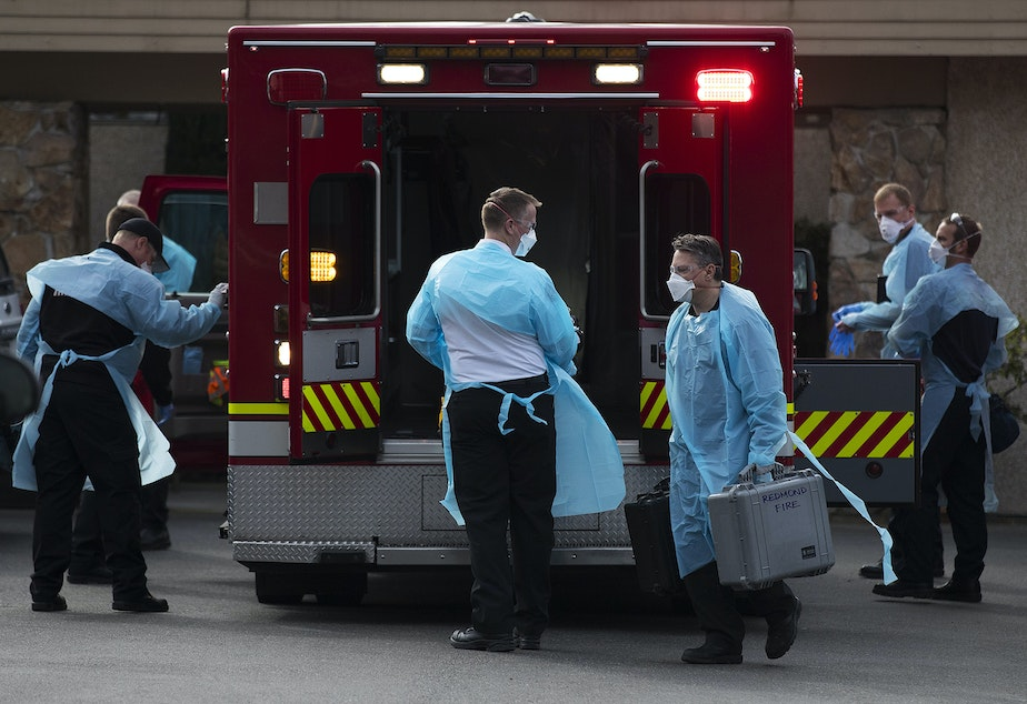 caption: First responders and members of the Kirkland Fire Department arrive at the Life Care Center of Kirkland to transport a resident to the hospital on Thursday, March 5, 2020, in Kirkland.