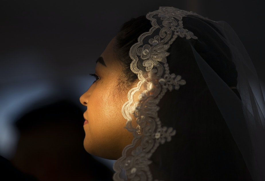 caption: Light shines on Janeli Alcala's face during a mass wedding ceremony for 23 couples on Sunday, June 2, 2019, at Our Lady of the Desert Church in Mattawa.