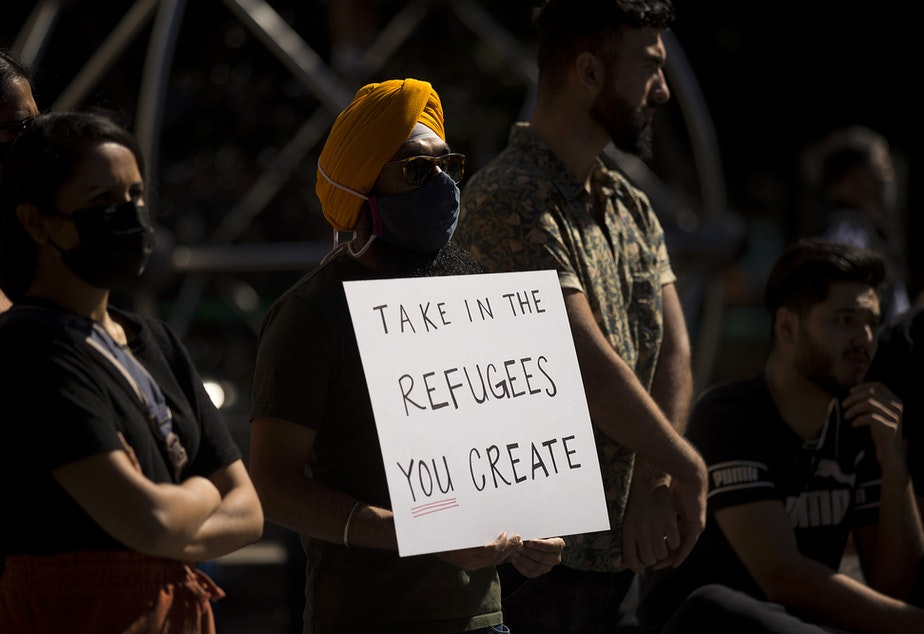 caption: Angad Singh holds a sign that reads, 'Take in the refugees you create,' while attending a rally and march in solidarity with Afghans on Saturday, August 28, 2021, at Westlake Park in Seattle.