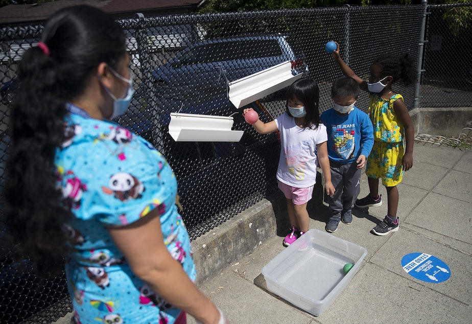 caption: Students play a game with teacher Margarita Arias, left, on the playground after collecting flowers on a walk, on Thursday, July 16, 2020, at the Denise Louie Education Center along Beacon Avenue South in Seattle.