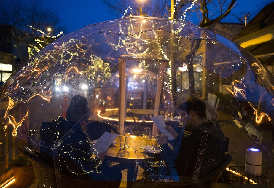 caption: Customers look at menus while dining inside of a clear dome structure outside of San Fermo on Sunday, November 15, 2020, along Ballard Avenue Northwest in Seattle. New statewide restrictions, including a ban on indoor dining beginning Wednesday, were announced by Gov. Jay Inslee on Sunday to curb the rapid spread of Covid-19.