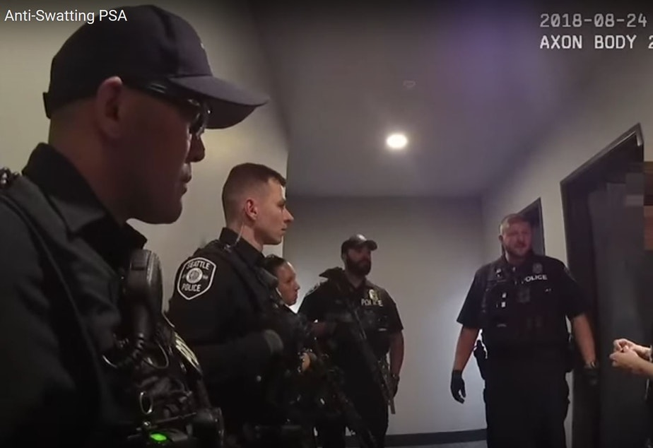 "Seattle police officers talk to a victim of ""swatting"" -- a hoax 911 call."