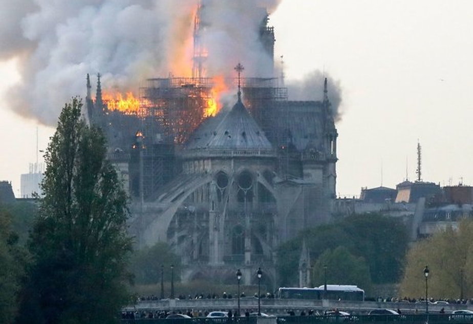 Smoke ascends as flames rise during a fire at the landmark Notre Dame Cathedral in central Paris on April 15, 2019.