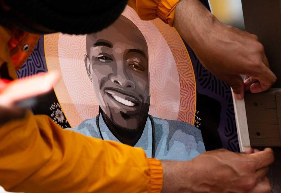 """caption: Community members gathered in June for a celebration of life for Manuel Ellis, who was killed by Tacoma police in March. In this photo, one of the attendees hangs a flyer with Ellis' image that says """"Happy Father's Day Manny."""""""