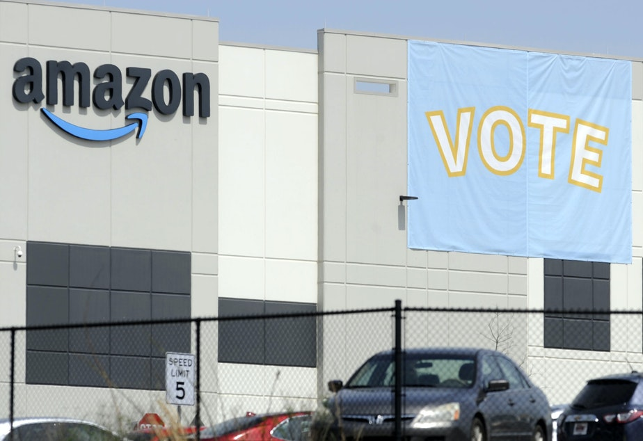caption: A banner encourages workers to vote in a union election at Amazon's warehouse in Bessemer, Ala.