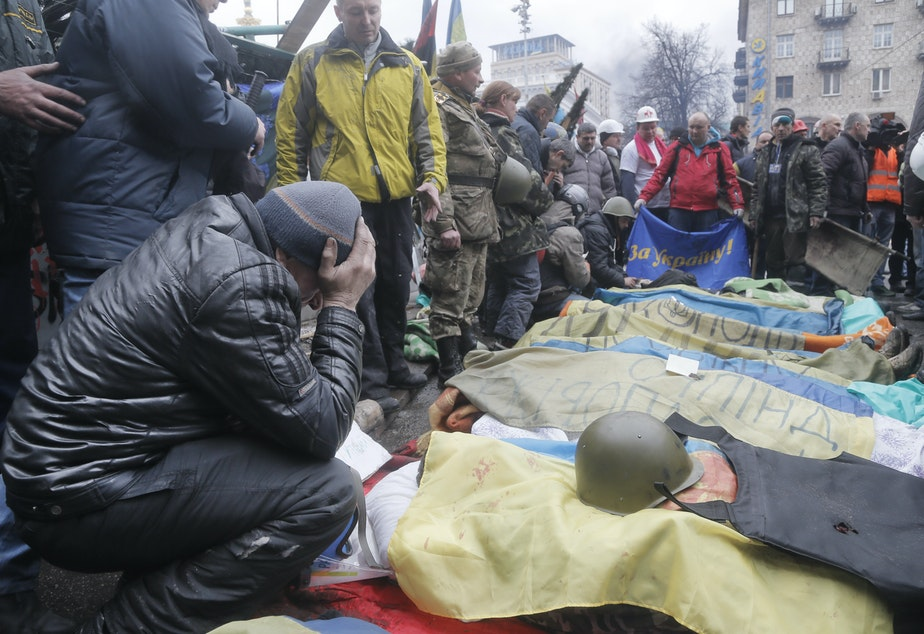 caption: Activists pay respects to protesters killed in clashes with police, during clashes with riot police in Kiev's Independence Square, the epicenter of the country's current unrest.
