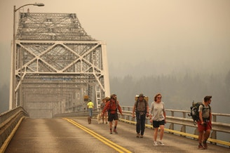 Pedestrians walk off the Bridge of the Gods, which spans the Columbia River between Washington and Oregon, as smoke from the Eagle Creek Fire obscures the Oregon hills in the background near Stevenson, Washington, Wednesday, Sept. 6, 2017.