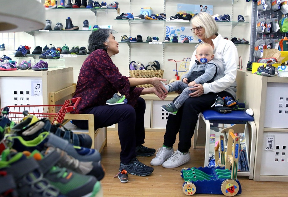 caption: Sarah Stegner (L) helps a customer at her store, Kid Friendly Footwear @ Again and Again. Stegner can't keep employees around due to the high cost of housing.