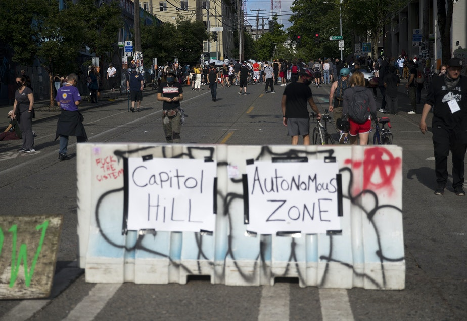 caption: Barriers are set up at the intersection of 11th Avenue and East Pine Street at the 'Capitol Hill Autonomous Zone,' also known as CHAZ, on Wednesday, June 10, 2020, in Seattle.