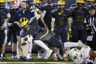 Bellevue running back Isaiah Gilchrist, left, leaps to avoid a tackle attempt by Eastside Catholic's Noah Failauga during the first half of the Class 3A high school football championship Friday, Dec. 4, 2015.