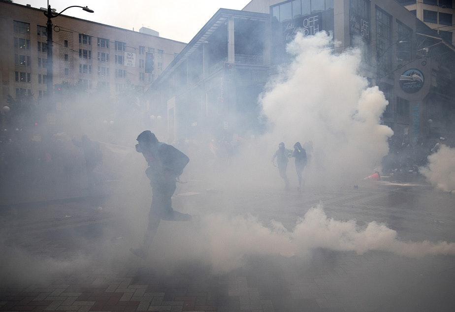 caption: Protesters run through tear gas and flash bombs on Saturday, May 30, 2020, at the intersection of 5th and Pine Streets in Seattle. Thousands gathered in a protest that turned violent following the violent police killing of George Floyd, a black man who was killed by a white police officer who held his knee on Floyd's neck for 8 minutes and 46 seconds, as he repeatedly said, 'I can't breathe,' in Minneapolis on Memorial Day.