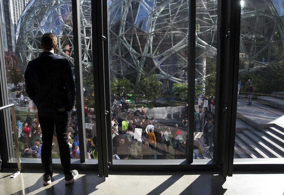 caption: An Amazon employee watches a 'Stop Bezos from Buying this Election rally' on Thursday, October 24, 2019, at Amazon's spheres in Seattle.