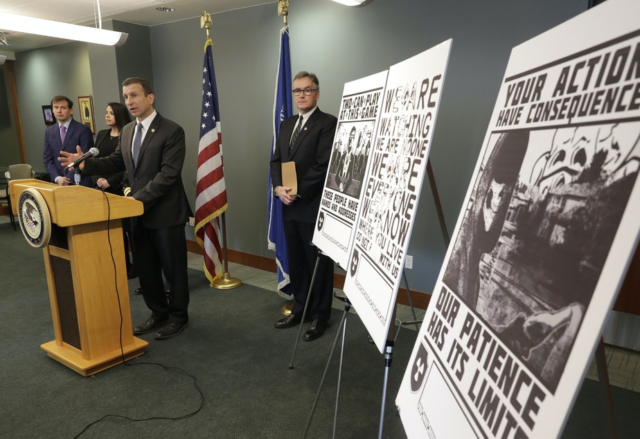 caption: Raymond Duda, FBI Special Agent in Charge in Seattle, speaks in February 2020 about charges against a group of alleged members of the neo-Nazi group Atomwaffen Division for cyber-stalking and mailing threatening communications, including the posters at right, in a campaign against journalists in several cities.