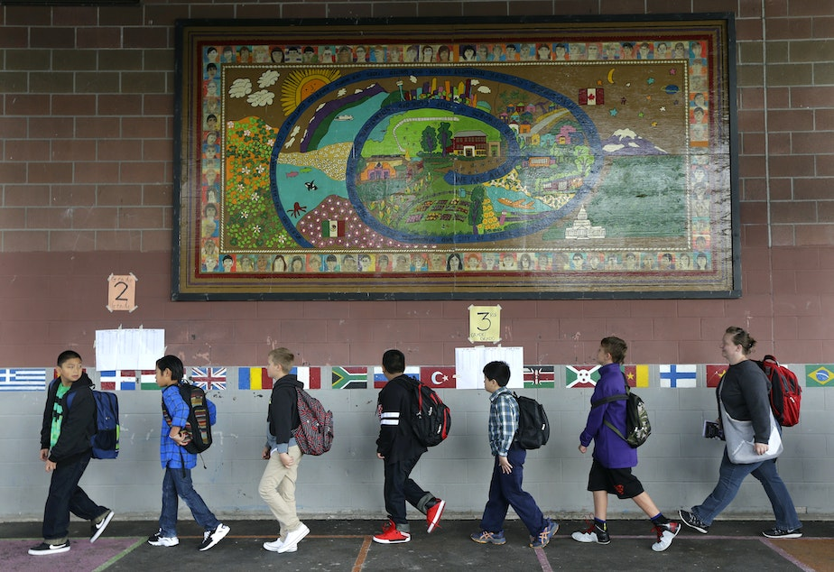 Students walk past a mural at Concord International School, Thursday, Sept. 17, 2015, in Seattle.