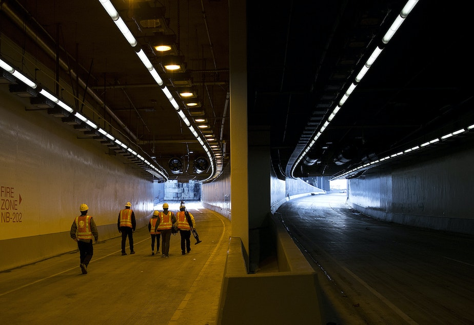 caption: Members of the media walk toward the the tunnel's northbound on-ramp, left, on Thursday, November 15, 2018, inside the State Route 99 tunnel in Seattle.