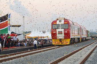 People cheer and throw confetti after Kenyan President Uhuru Kenyatta flags off a cargo train for its inaugural journey to Nairobi last year at the port of the coastal town of Mombasa.