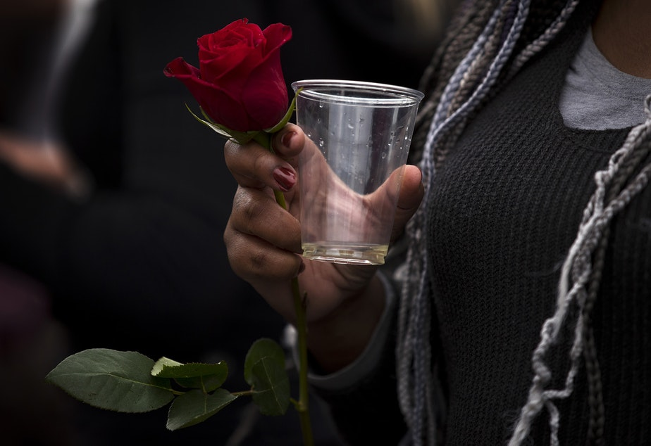 caption: Christina Shook holds a rose while drinking champagne during an impromptu celebration after Joe Biden was officially named the president elect on Saturday, November 7, 2020, at the intersection of 10th Avenue and East Pine Street in Seattle.