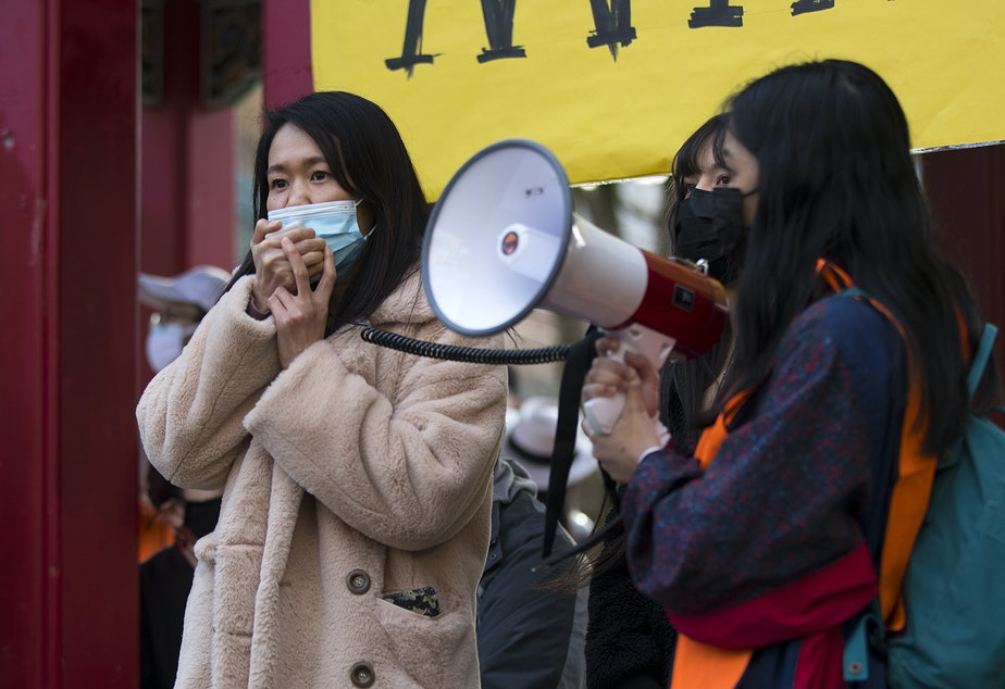 caption: Noriko Nasu, left, speaks to the crowd during the 'We Are Not Silent' rally against anti-Asian hate and bias on March 13, 2021 at Hing Hay Park in Seattle. Nasu was  attacked last month in the Chinatown International-District. Several days of actions are planned by rally organizers in the Seattle area following recent attacks and violence against Asian Americans and Pacific Islanders.
