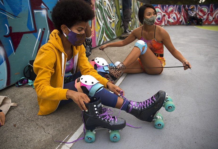 caption: Dalila Gittens, left, and Celina Macadangdang, medical residents at a Seattle-area hospital, untie their roller-skates after skating on Tuesday, September 22, 2020, at the Judkins Park sports courts in Seattle.