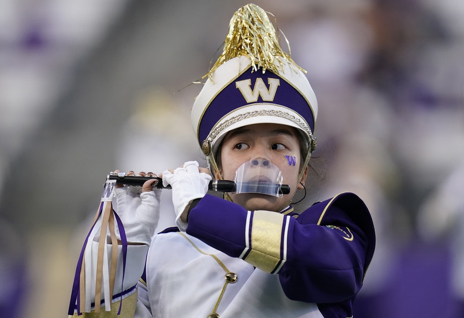 caption: A piccolo player with the Washington Marching Band performs with a mouth shield due to the COVID-19 pandemic before an NCAA college football game against California, Saturday, Sept. 25, 2021, in Seattle.