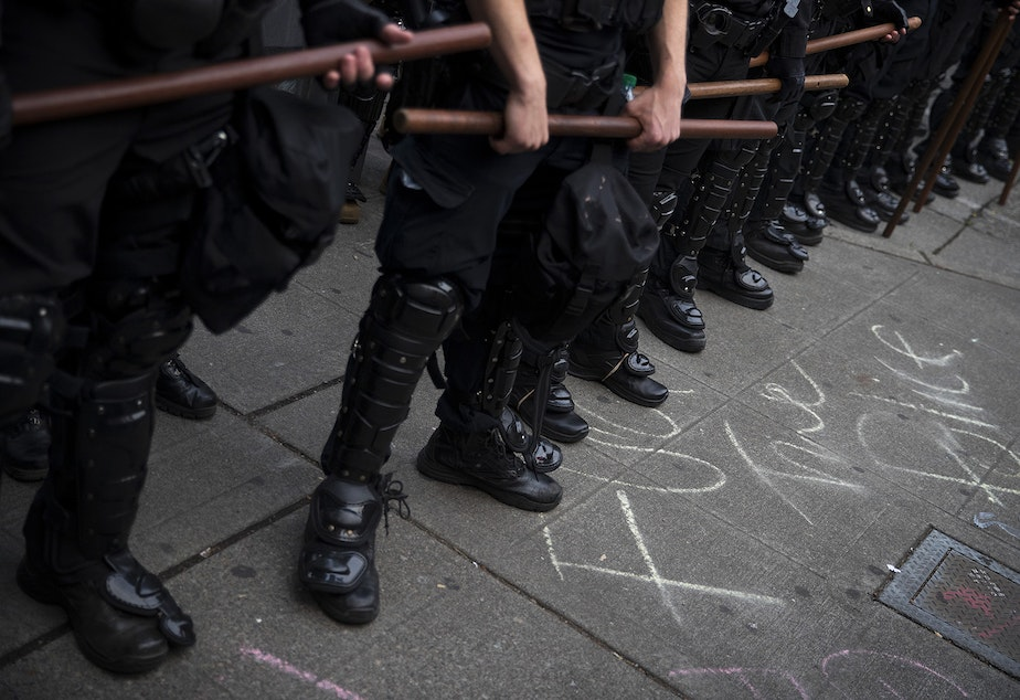 caption: Seattle police officers hold their batons while standing in a police line next to chalk writing on the sidewalk that says 'fuck the police,' on the fifth day of protests following the violent police killing of George Floyd on Tuesday, June 2, 2020, at the intersection 11th and Pine Streets in Seattle.