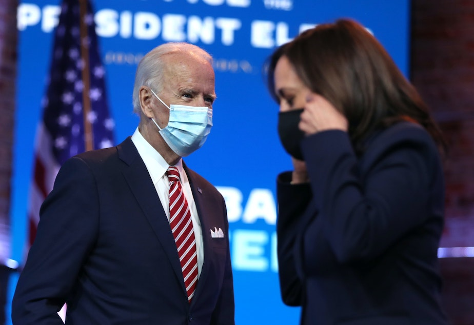 caption: President-elect Joe Biden walks by Vice President-elect Kamala Harris before delivering remarks on his plan for economic recovery under his incoming administration.