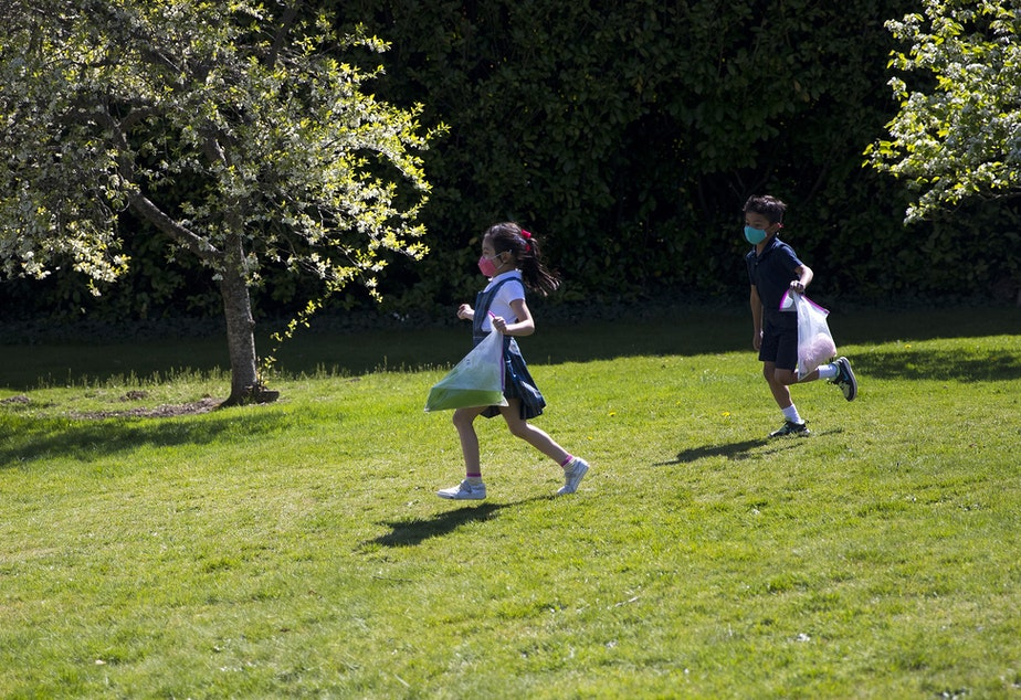 caption: Villa Academy kindergarten students Kez, left, and Riko, right, run toward their outdoor music class under a tent with teacher Emily Callan, not pictured, on Tuesday, April 20, 2021, at the school in Seattle.