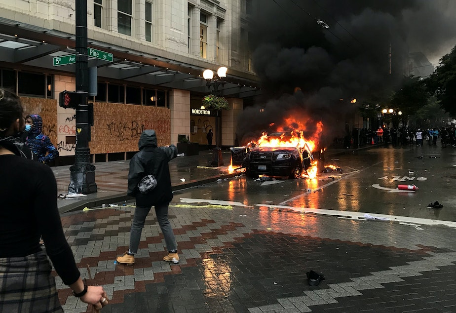 caption: A police car burns outside the Nordstrom in downtown Seattle on Saturday, May 30, 2020.