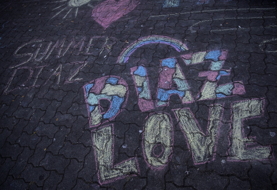 caption: Chalk drawings are shown next to a memorial for Summer Taylor and Diaz Love on Wednesday, July 22, 2020, at City Hall Park in Seattle.