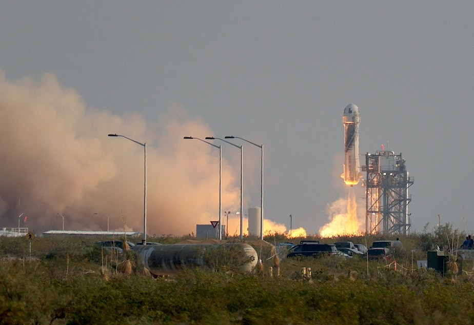 caption: The New Shepard Blue Origin rocket lifts-off from the launch pad carrying Jeff Bezos along with his brother Mark Bezos, 18-year-old Oliver Daemen, and 82-year-old Wally Funk prepare to launch on Tuesday in Van Horn, Texas. The crew are riding in the first human spaceflight for the company.