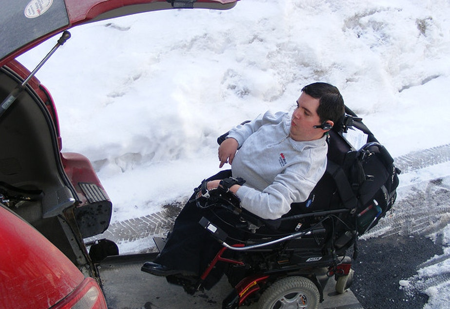 caption: FILE: A man with muscular dystrophy navigates snowy conditions.