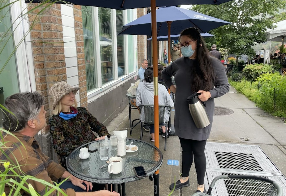 caption: Miki Sodos chats with customers outside Cafe Pettirosso on Capitol Hill in Seattle