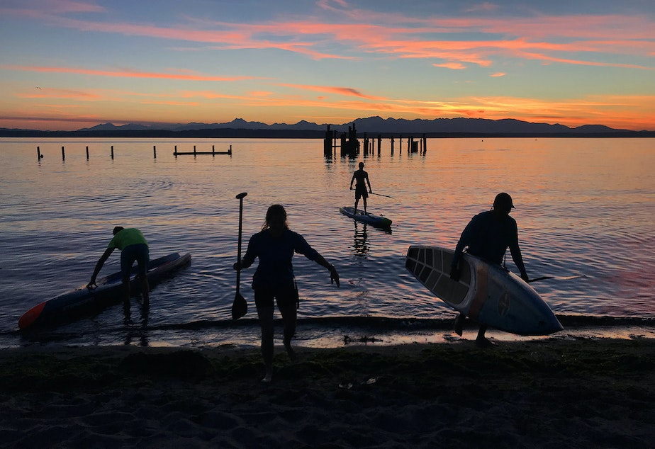 Paddleborders end their evening paddle on a small beach south of Golden Gardens Park on Monday, August 27, 2018, in Seattle.