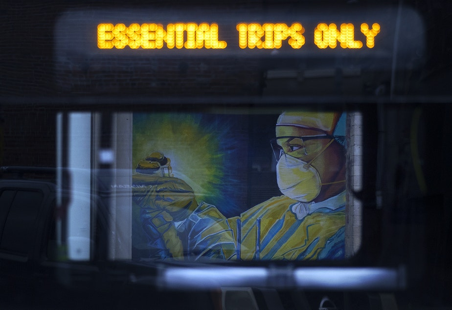 caption: A mural of a health care worker is shown through the window of a passing King County Metro bus on Tuesday, April 28, 2020, along South Main Street in Seattle.