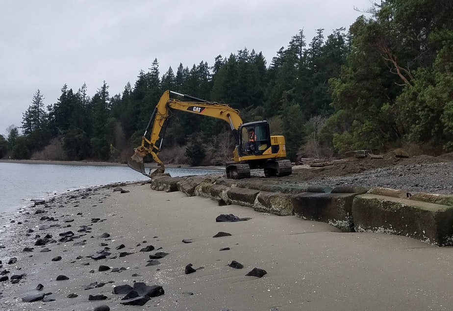 caption: An excavator removes concrete blocks that armor a beach on McNeil Island in south Puget Sound on Tuesday.