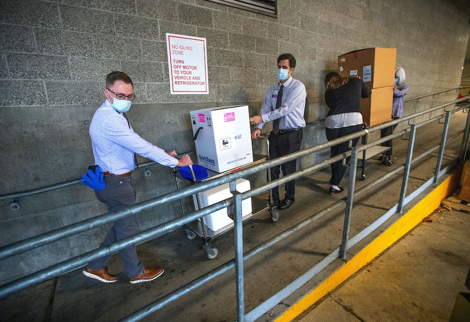 caption: University of Washington Medical Center Montlake campus pharmacy administration resident Derek Pohlmeyer, left, and UWMC pharmacy director Michael Alwan transport a box containing Pfizer-BioNTech COVID-19 vaccines toward a waiting vehicle headed to the UW Medical Center's other hospital campuses on Monday, Dec. 14, 2020, in Seattle.
