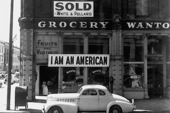 "A large sign reading ""I am an American"" is displayed in the window of a Japanese-owned grocery store, the day after the attack onPearl Harbor."