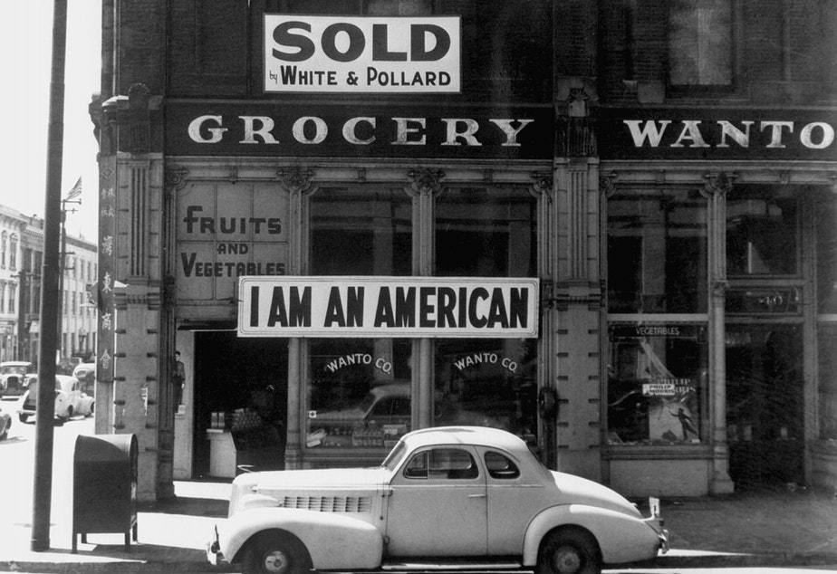 """A large sign reading """"I am an American"""" is displayed in the window of a Japanese-owned grocery store, the day after the attack onPearl Harbor."""
