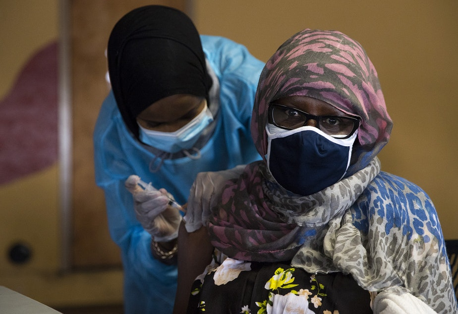 caption: Registered nurse Iman Yunis, left, administers the first dose of the Moderna Covid-19 vaccine for Jebbeh Freeman, right, on Wednesday, February 3, 2021, during a vaccine clinic set up by the Somali Health Board to vaccinate 100 seniors in the community at the Brighton Apartments complex on Rainier Avenue South in Seattle.