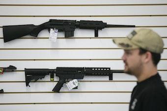 In this Dec. 9, 2015, photo, a sales associate walks past semiautomatic rifles at Bullseye Sport gun shop in Riverside, Calif.